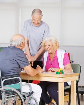 Glückliche Senioren in der Reha spielen gemeinsam Bingo
